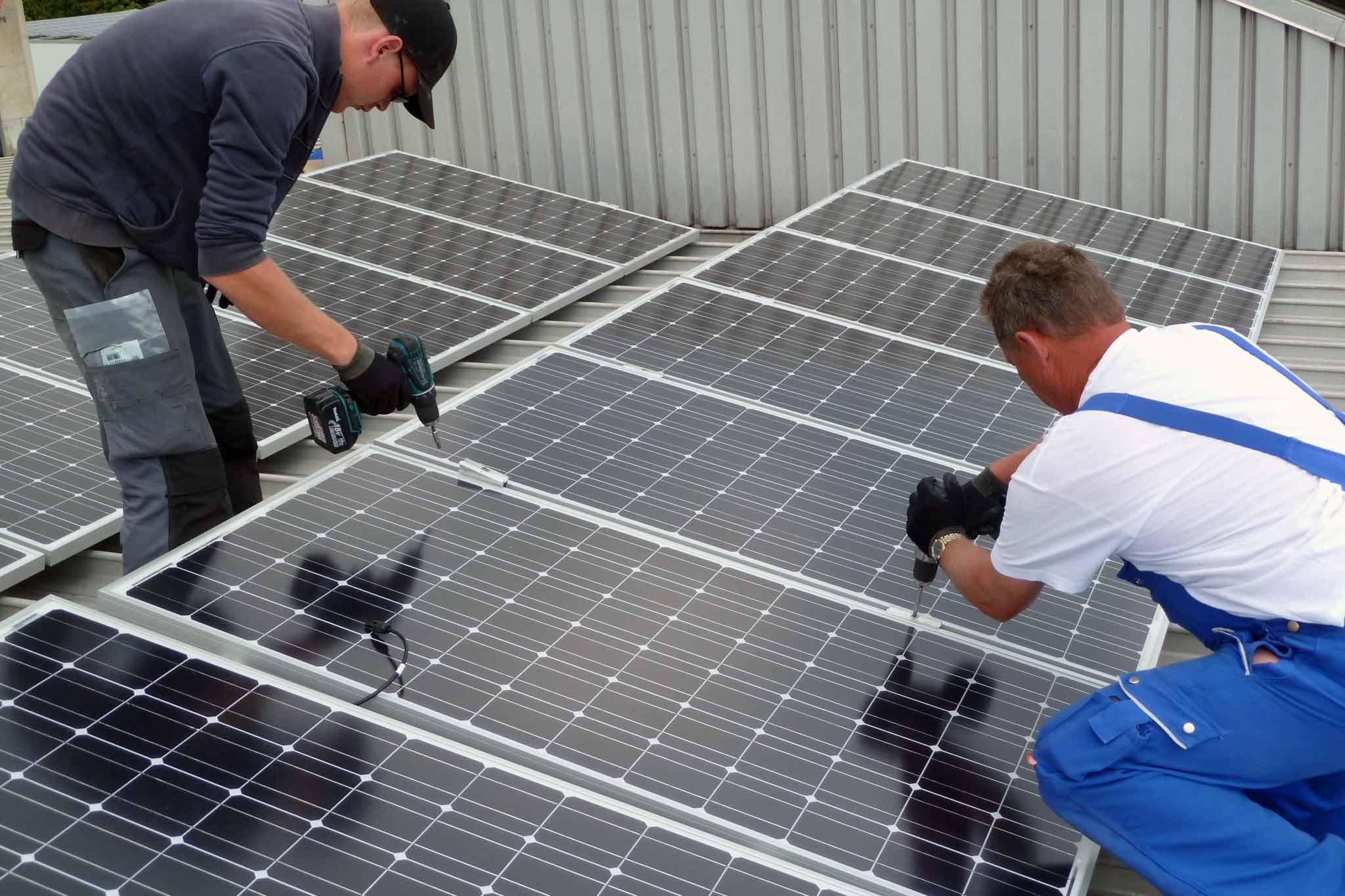 Zwei Männer beim Montieren einer Photovoltaik-Anlage