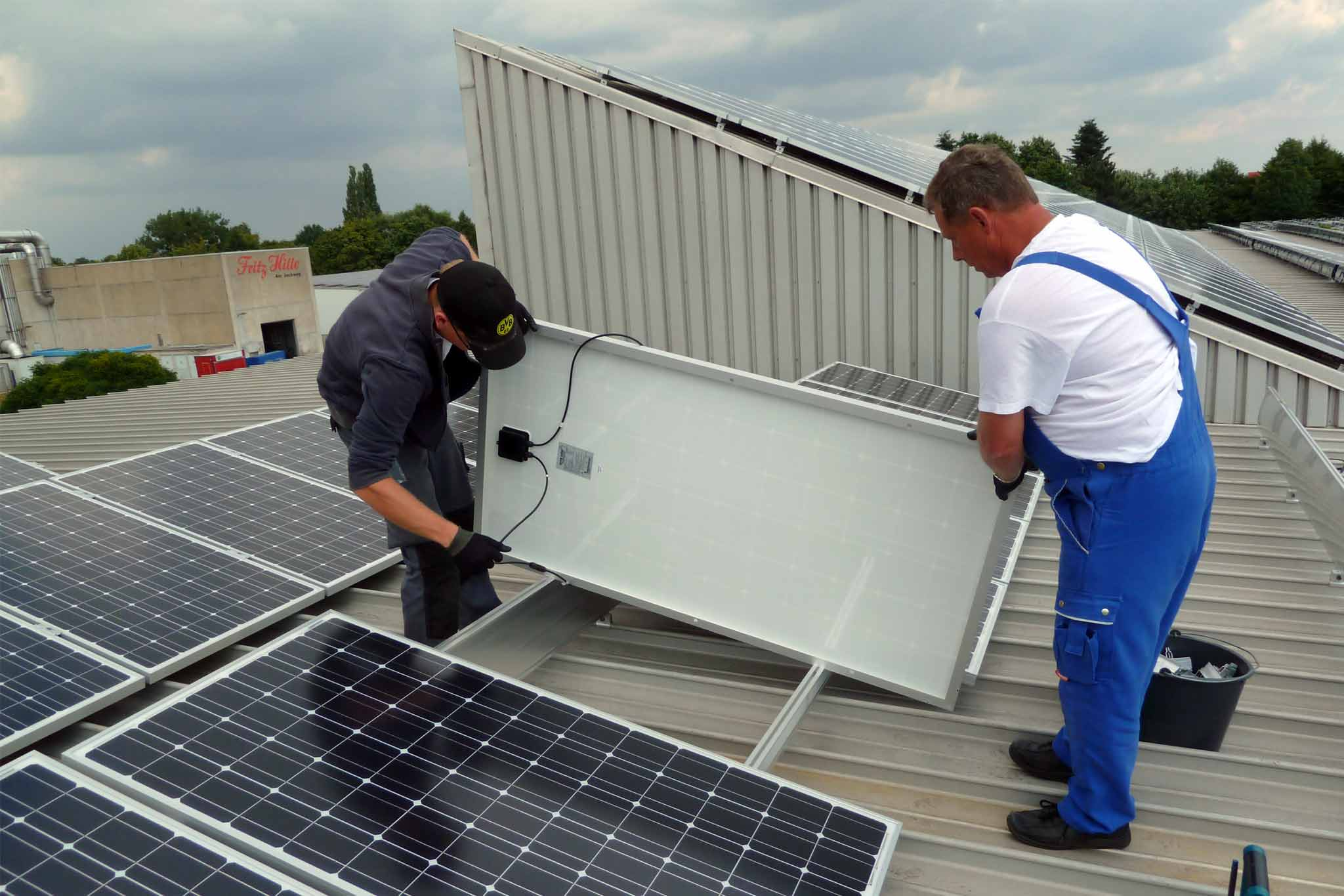 Personen beim Montieren einer Photovoltaik-Anlage